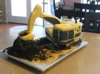 My nephew's Excavator Cake - Yes, it is a mess. It was very hot and I rolled the fondant too thin so it just started melting. The poor scoop is backwards! Can't believe I did that.