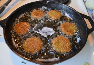 Carefully drop falafel patties into hot oil.