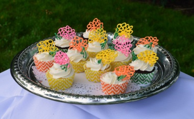 Vanilla cupcakes with buttercream frosting and simple chocolate flower decorations