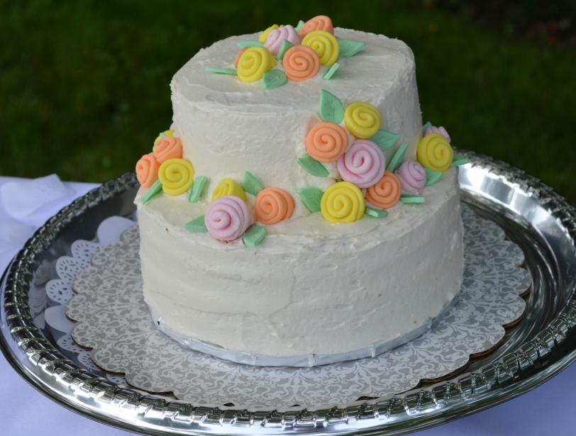 Simple wedding cake with buttercream frosting and rolled fondant flowers.