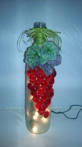 red grapes lighted wine bottle